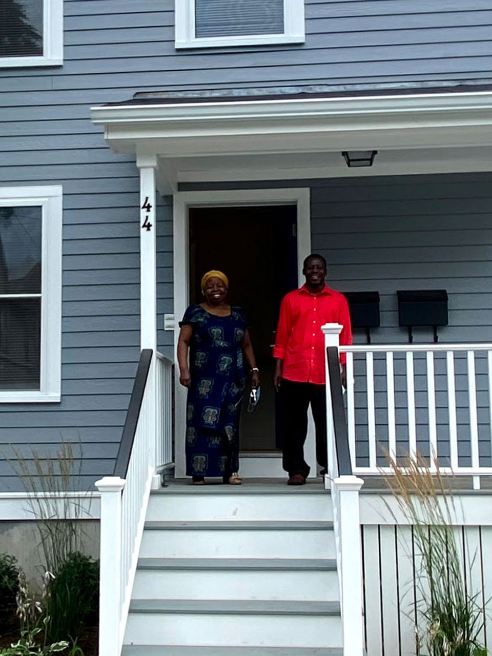 Happy new home owners stading on the front porch.