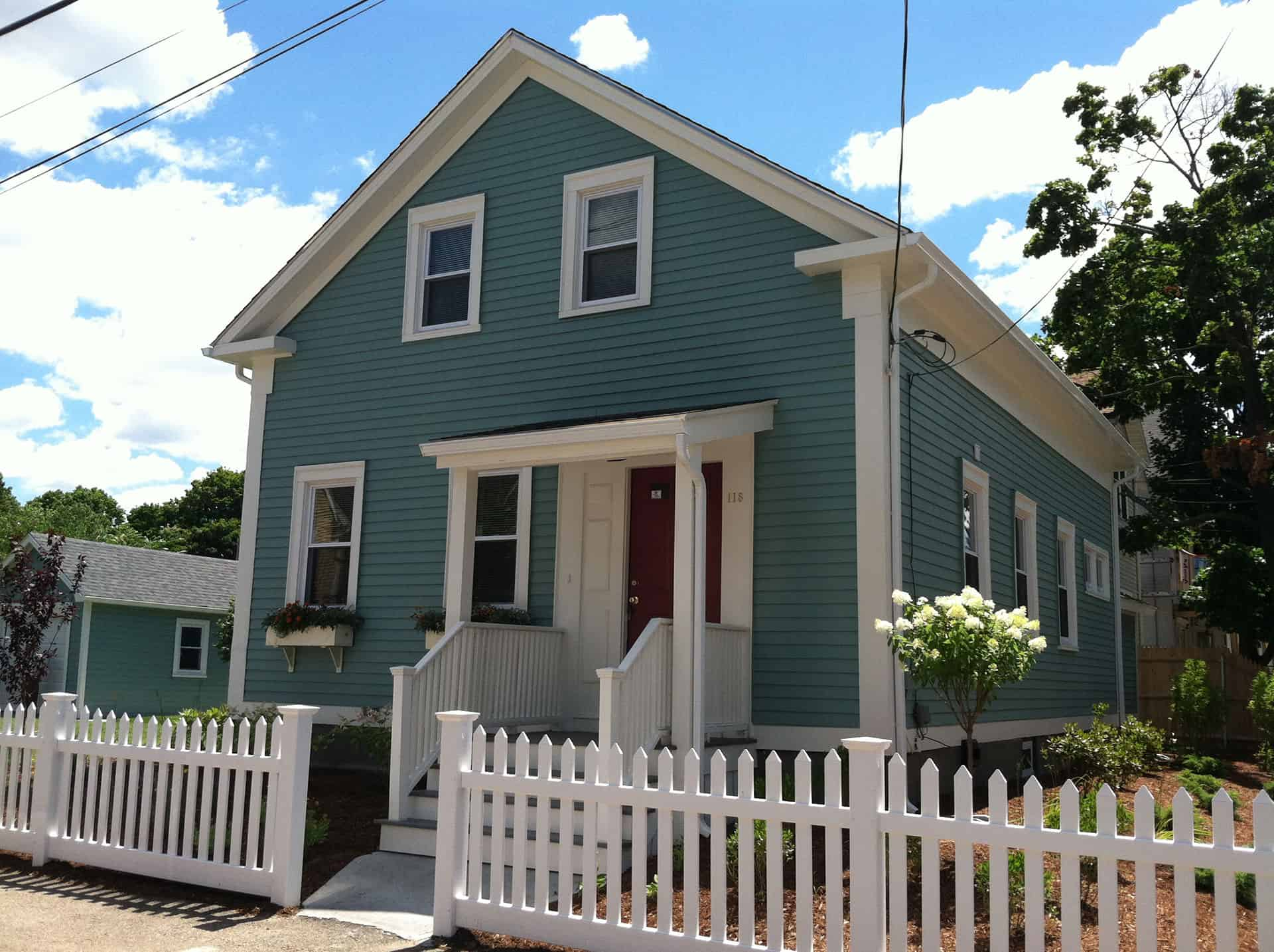 Green one and a half story home with window boxes and a picket fence.