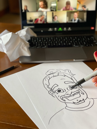 A photo of a hand drawing an illustration of a face.