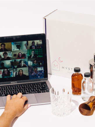A photo of a virtual group chat on a computer screen next to the contents of a Mystery box on the table.