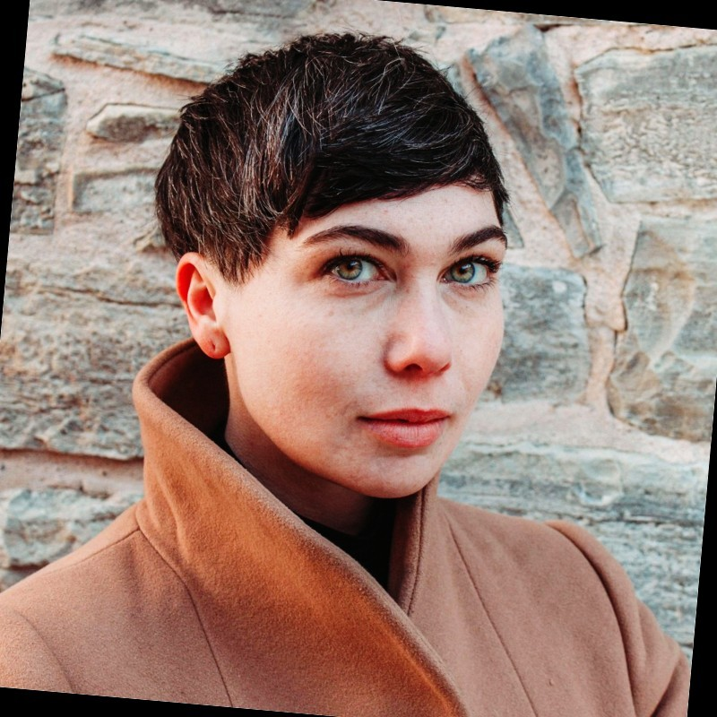 A head shot of a woman with short, dark hair wearing a camel coloured, wool coat standing in front of a stone wall.