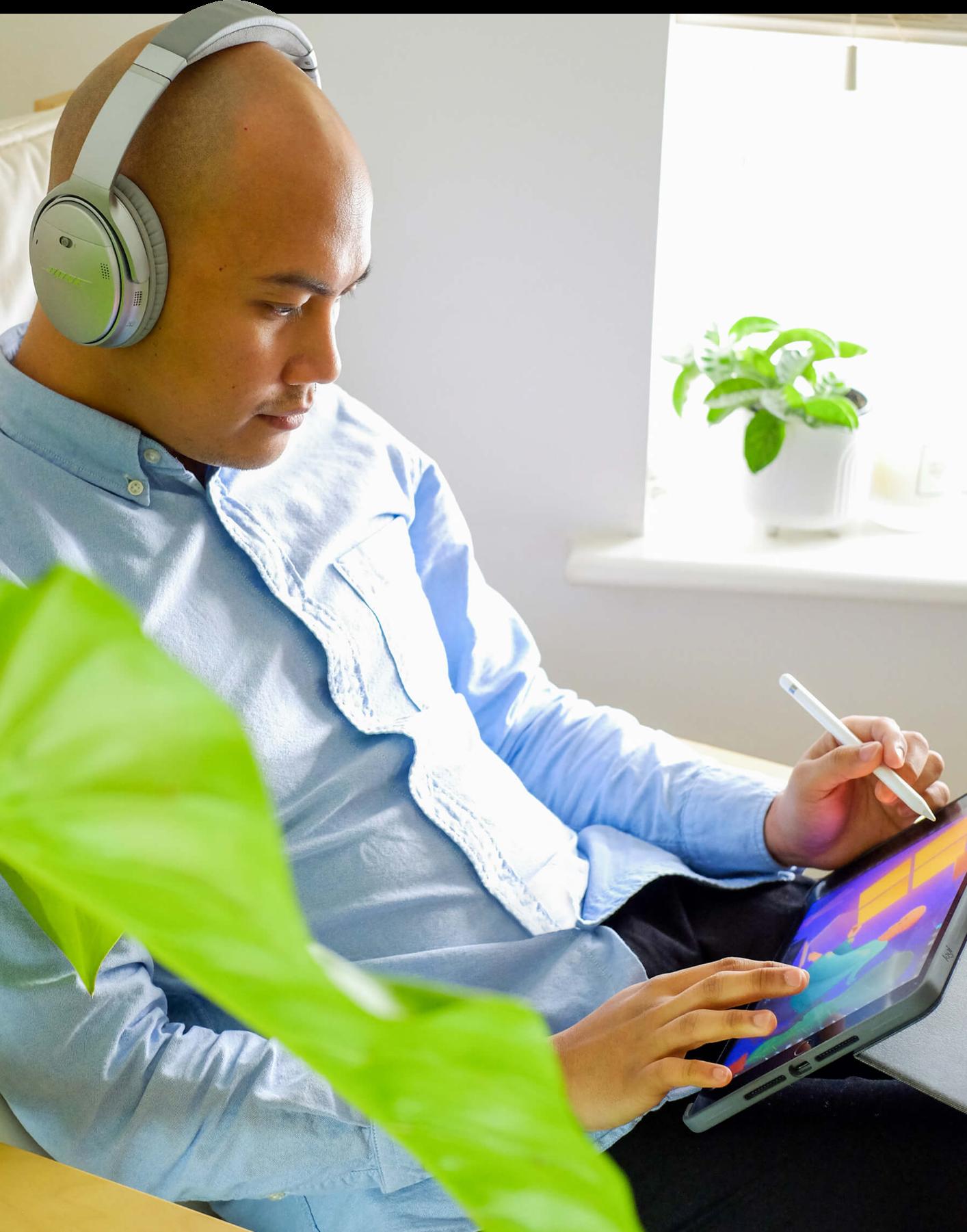 Eli wearing headphones, drawing on his iPad