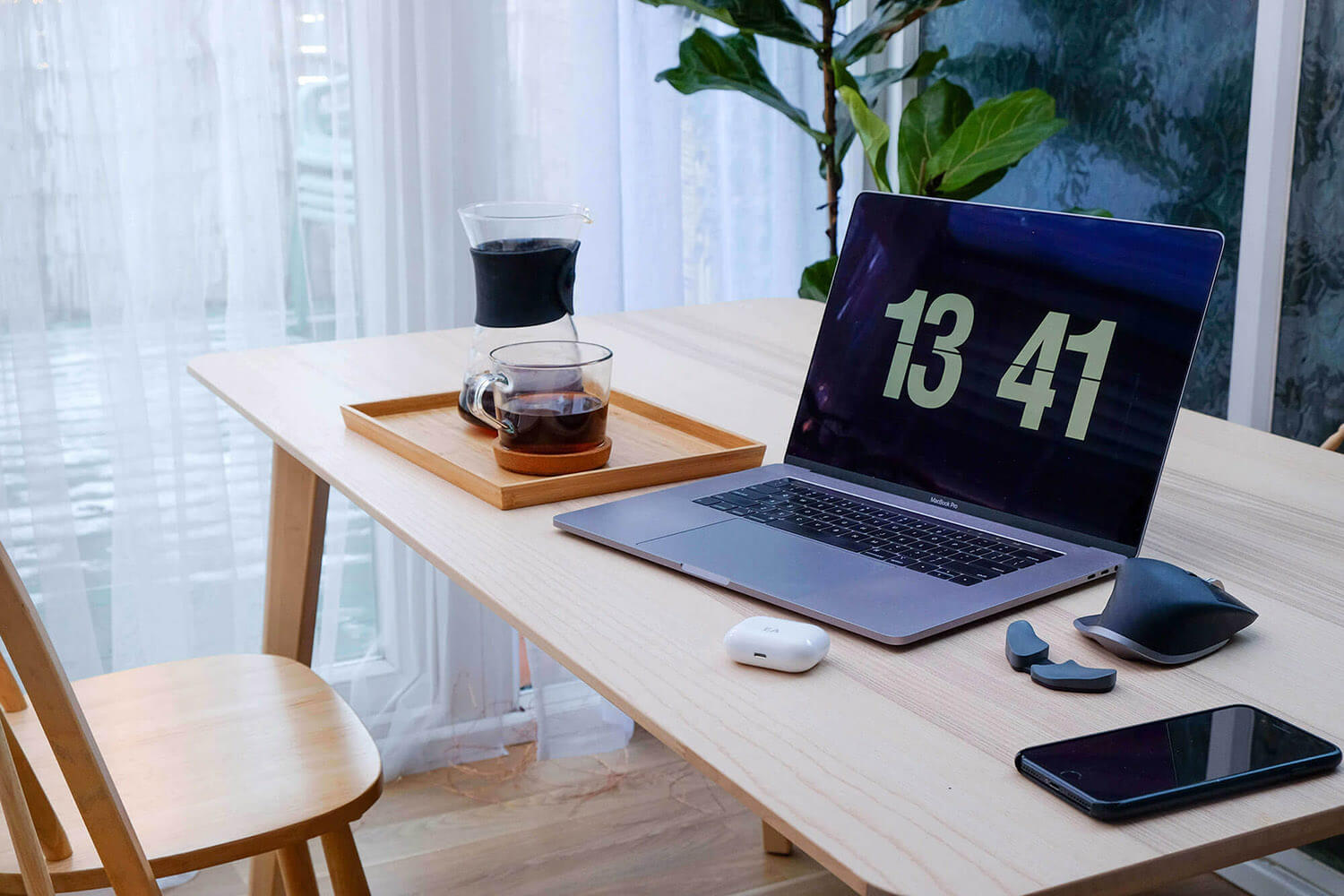 Eli's laptop on a table, next to a carafe filled with coffee