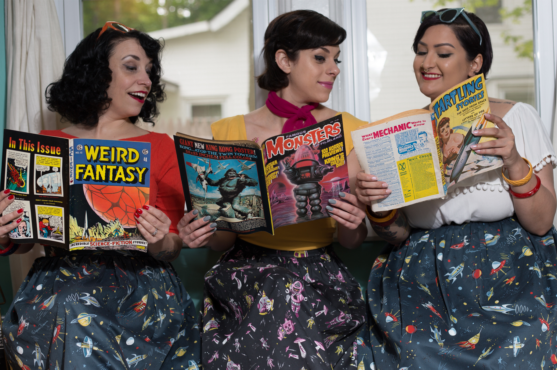 Photo of three people wearing Kitschy Witch Dresses and reading vintage sci-fi magazines