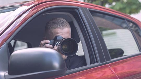 Detektiv - Beobachtung im Auto durch eine Kamera.