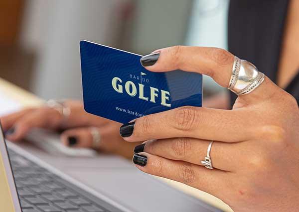 Fotografia de uma recepcionista segurando o cartão de comanda do Bar do Golfe.