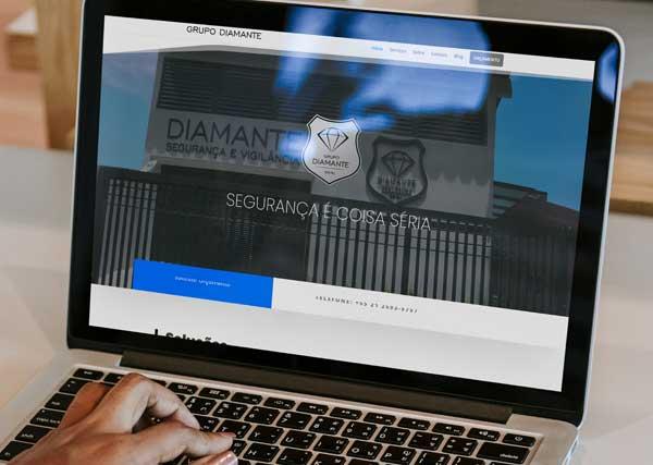 Imagem de pessoa utilizando o computador, exibindo o website da empresa Diamante Segurança e Vigilância.