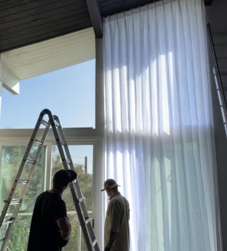 Professional team installing window furnishing