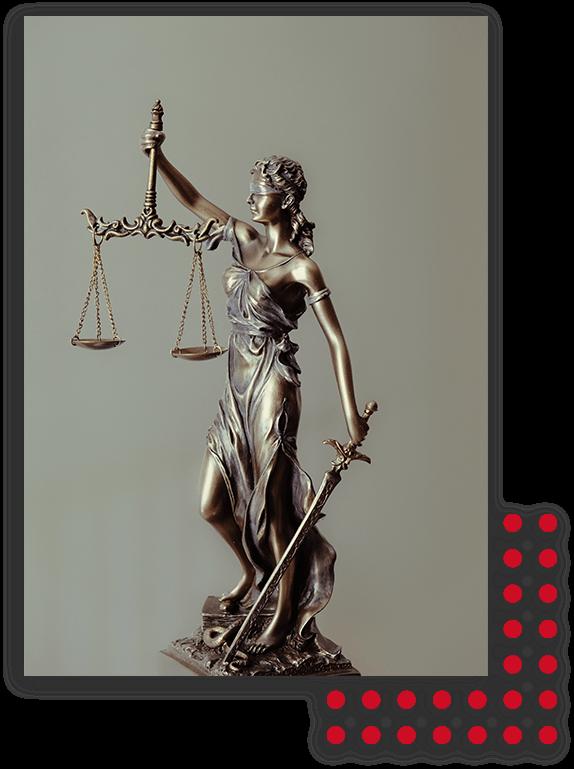 Ein Bild von einer Justitia Metallfigur vor einem grau-grünen Hintergrund plaziert als Sinnbild für Gerechtigkeit im Arbeitsrecht