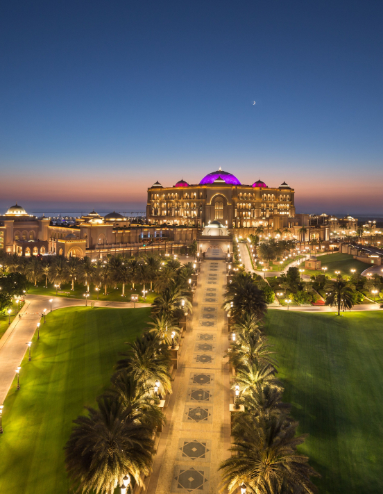 Aerial shot of a luxury hotel in Dubai at night time with the sun setting in the background.