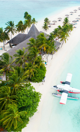 Sea plane parked up on turquoise blue waters next to a property on a white sand beach.