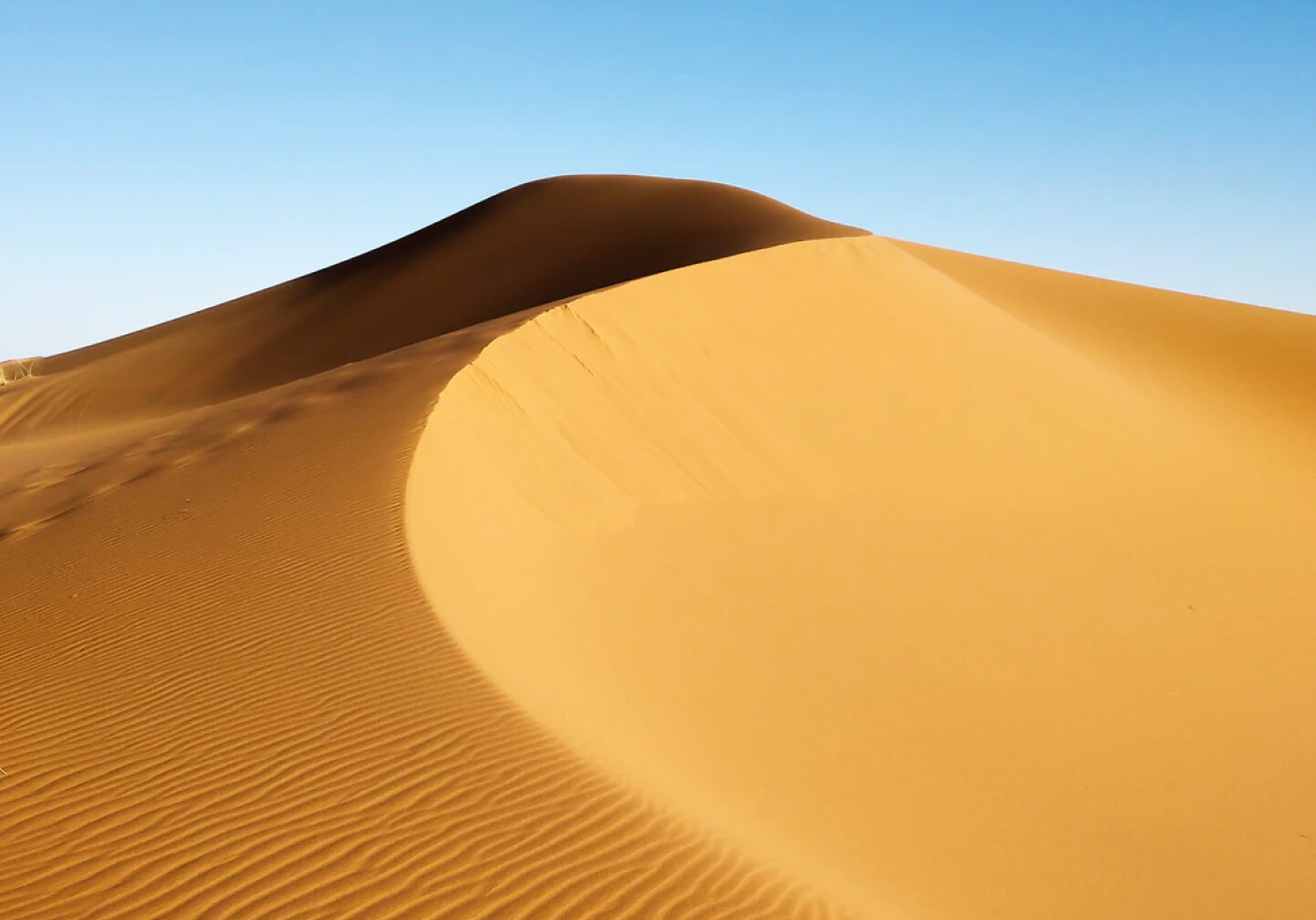 Yellow sand dune contrasting against a clear blue sky