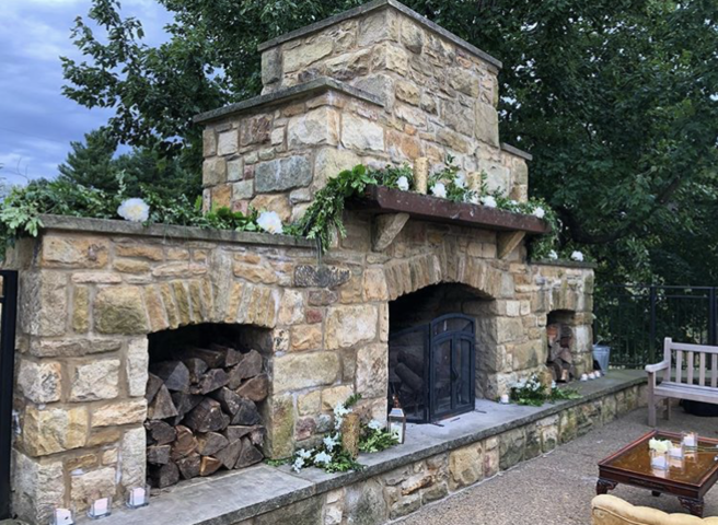 A grand outdoor fireplace with florals