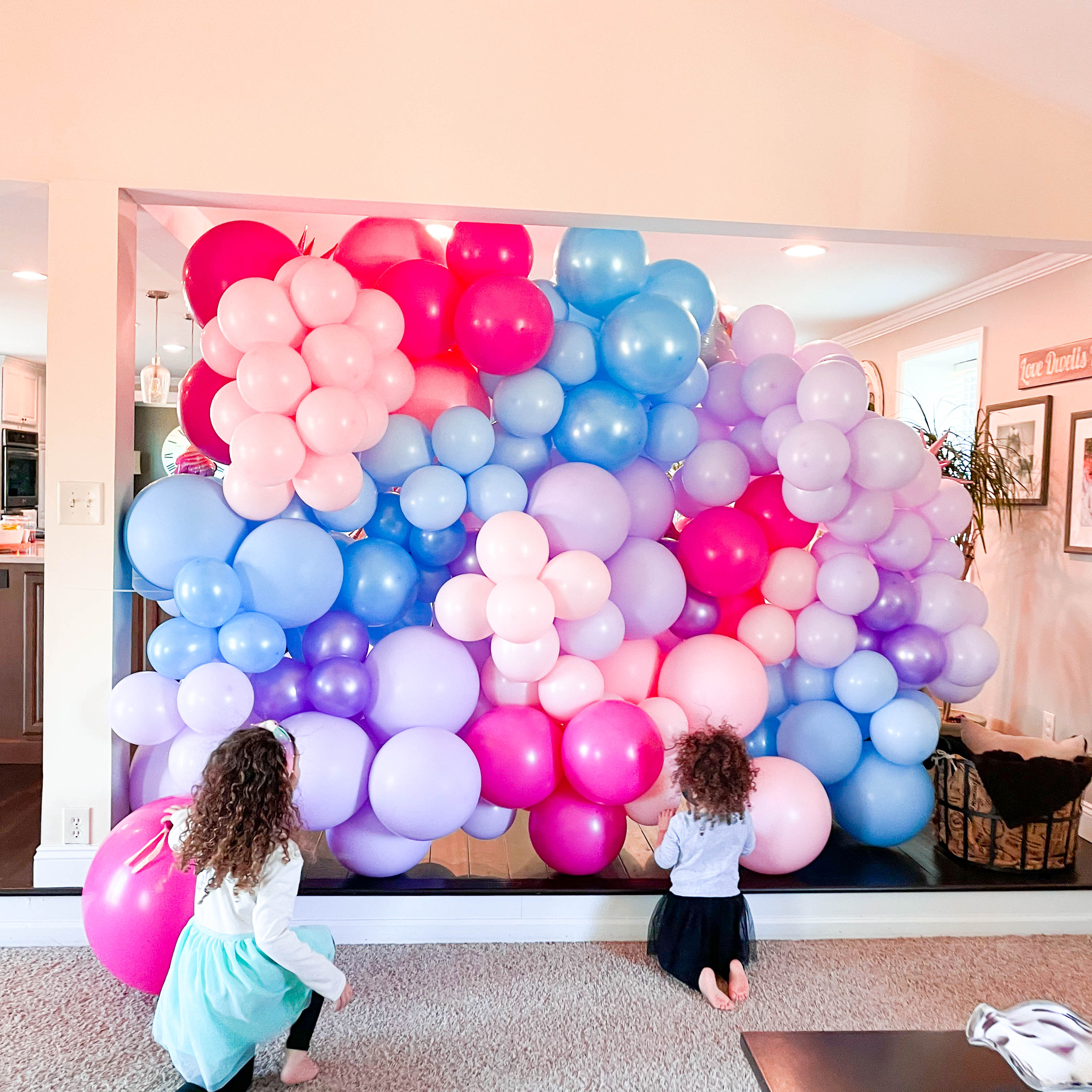 Two girls in front of pink, blue, and purple photo wall