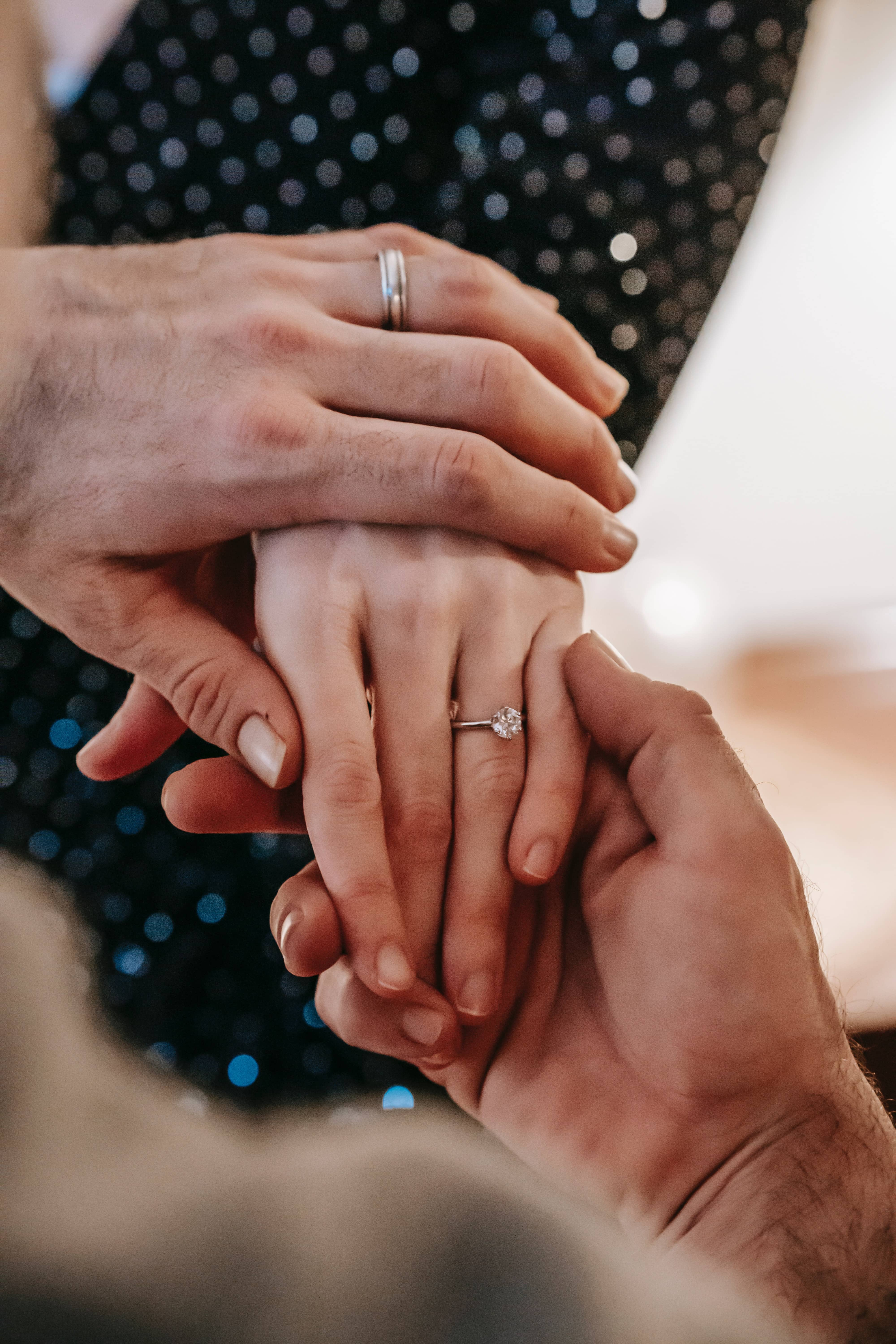 A man holding a woman's hand with an engagement ring