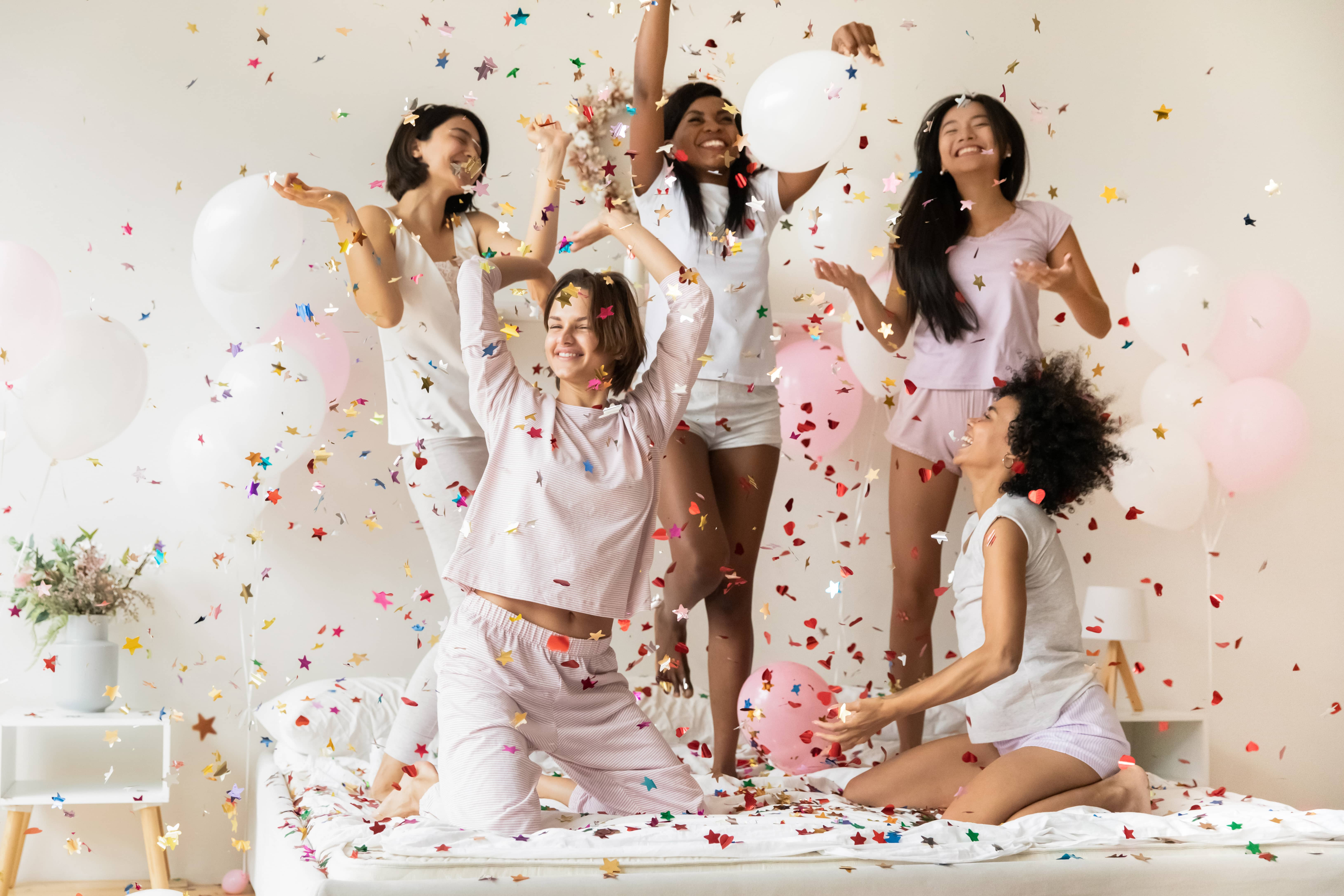 Five girls dancing on a bed with rainbow confetti and balloons