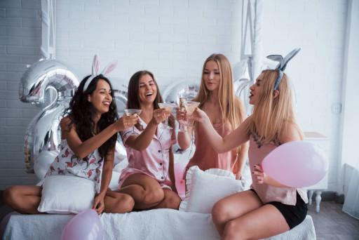 Four girls clinking drinks in pink pajamas