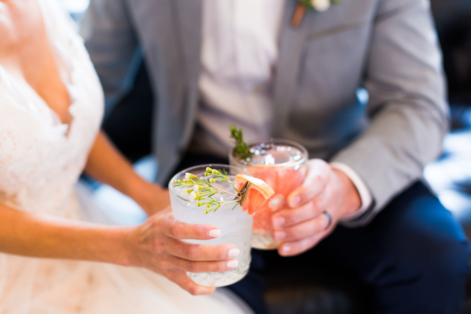 Bride and groom clinkling cocktails at a wedding