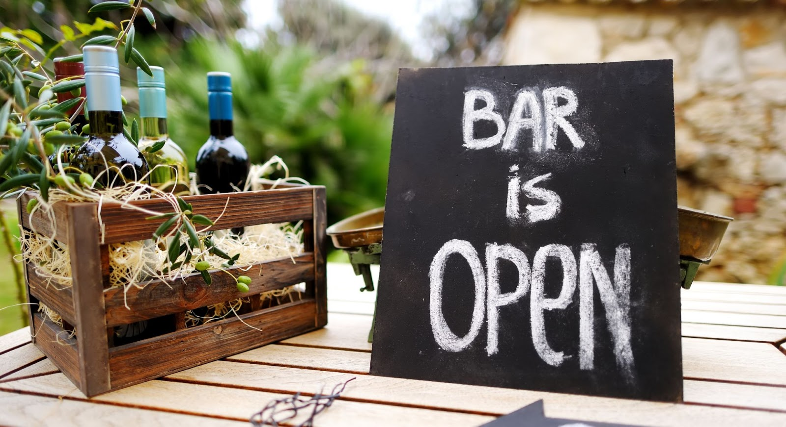 """Wine bottles in a basket with a """"Bar is open"""" sign"""