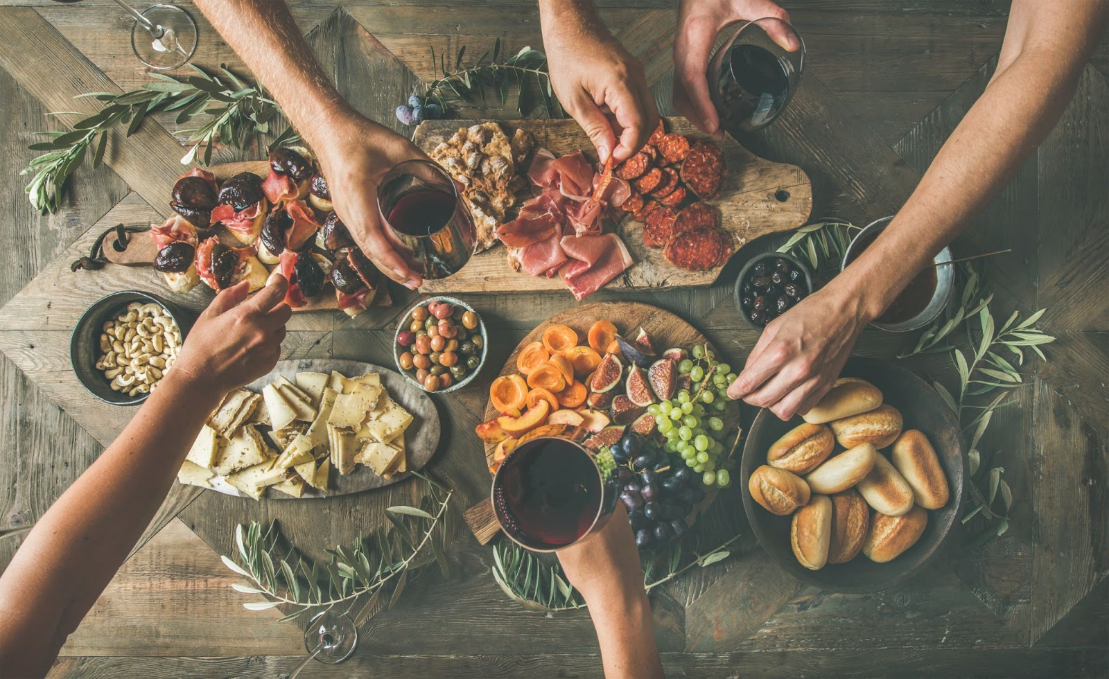 Charcuterie board with hands reaching to take food