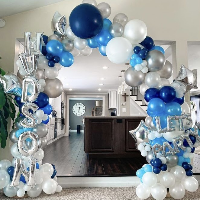 """A blue, silver, and white balloon arch that says """"Hudson"""" and """"Let's Party"""""""