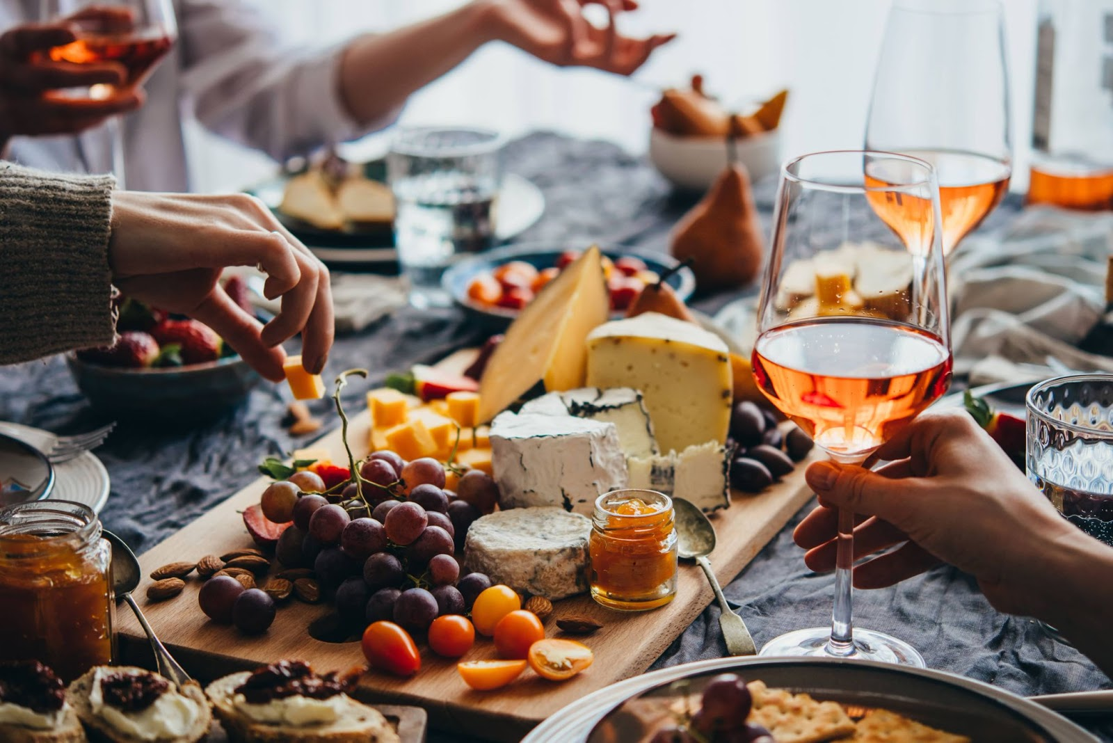 People sitting around a table with glasses of wine, fruit, and a charcuterie board