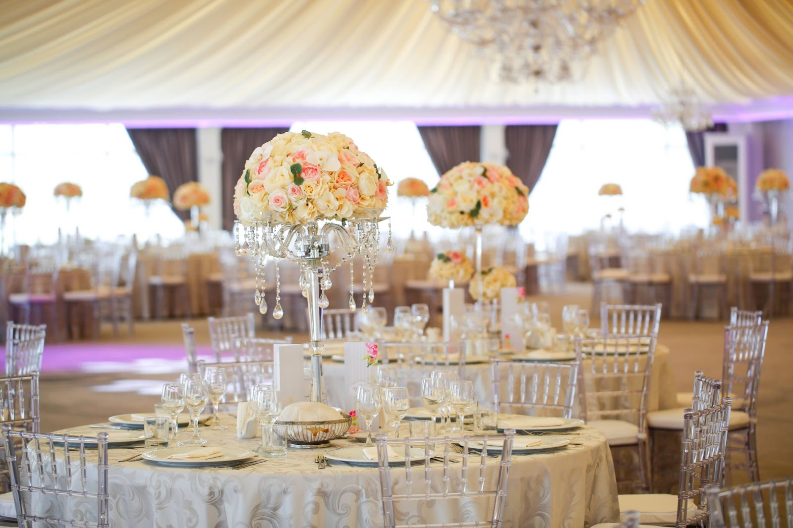 A wedding reception space with many tables and floral centerpieces.