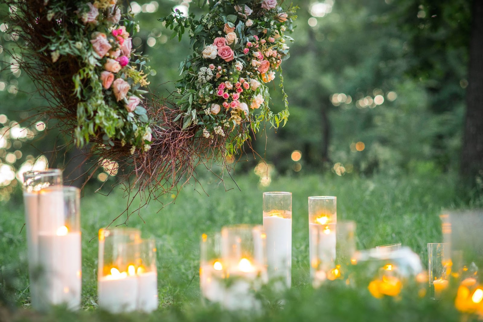 White candles and a decorative floral wreath at a casual wedding venue.