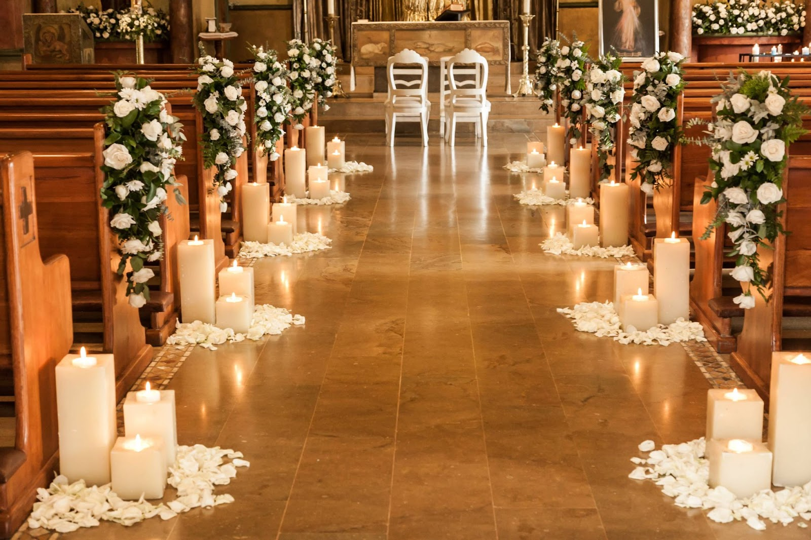 A church weddingisle with candles and flowers at the end of each pew.