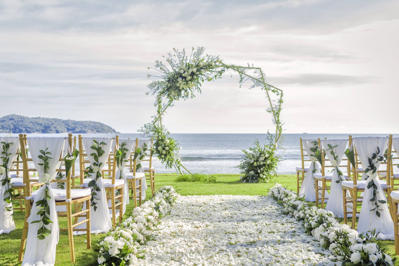 The isle of a beach wedding decorated with white flowers and greenery.