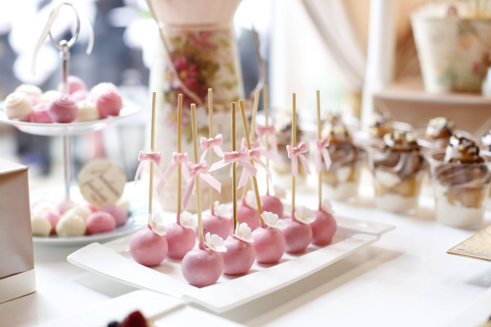 A dessert able with pink and white cake pops and truffles