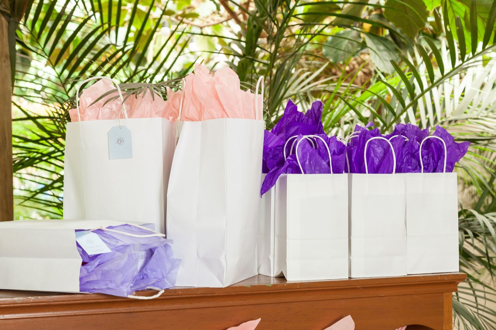 A table with white party favor bags with pink and purple tissue paper