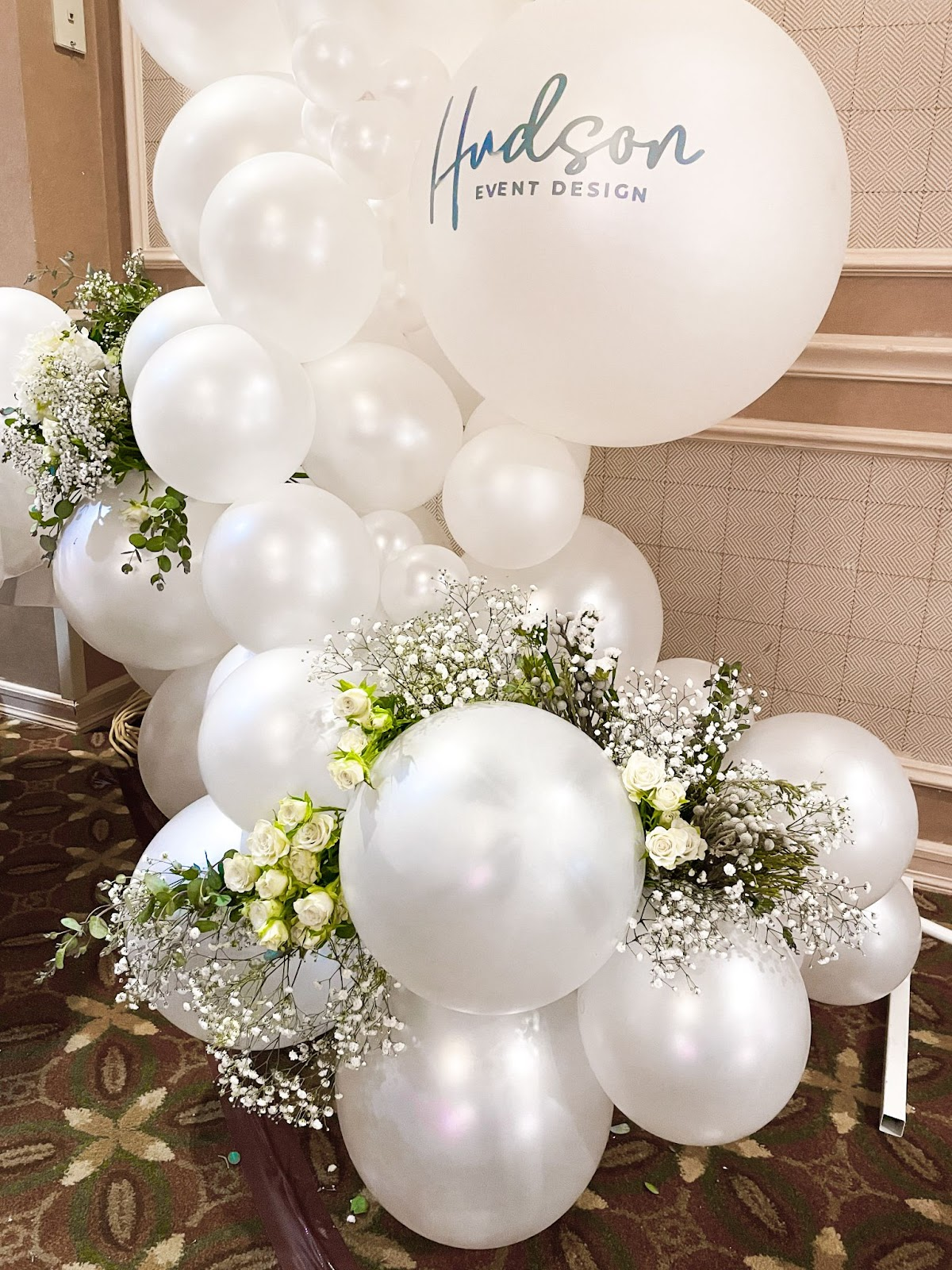 A white balloon garland with eucalyptus and white flowers attached into it
