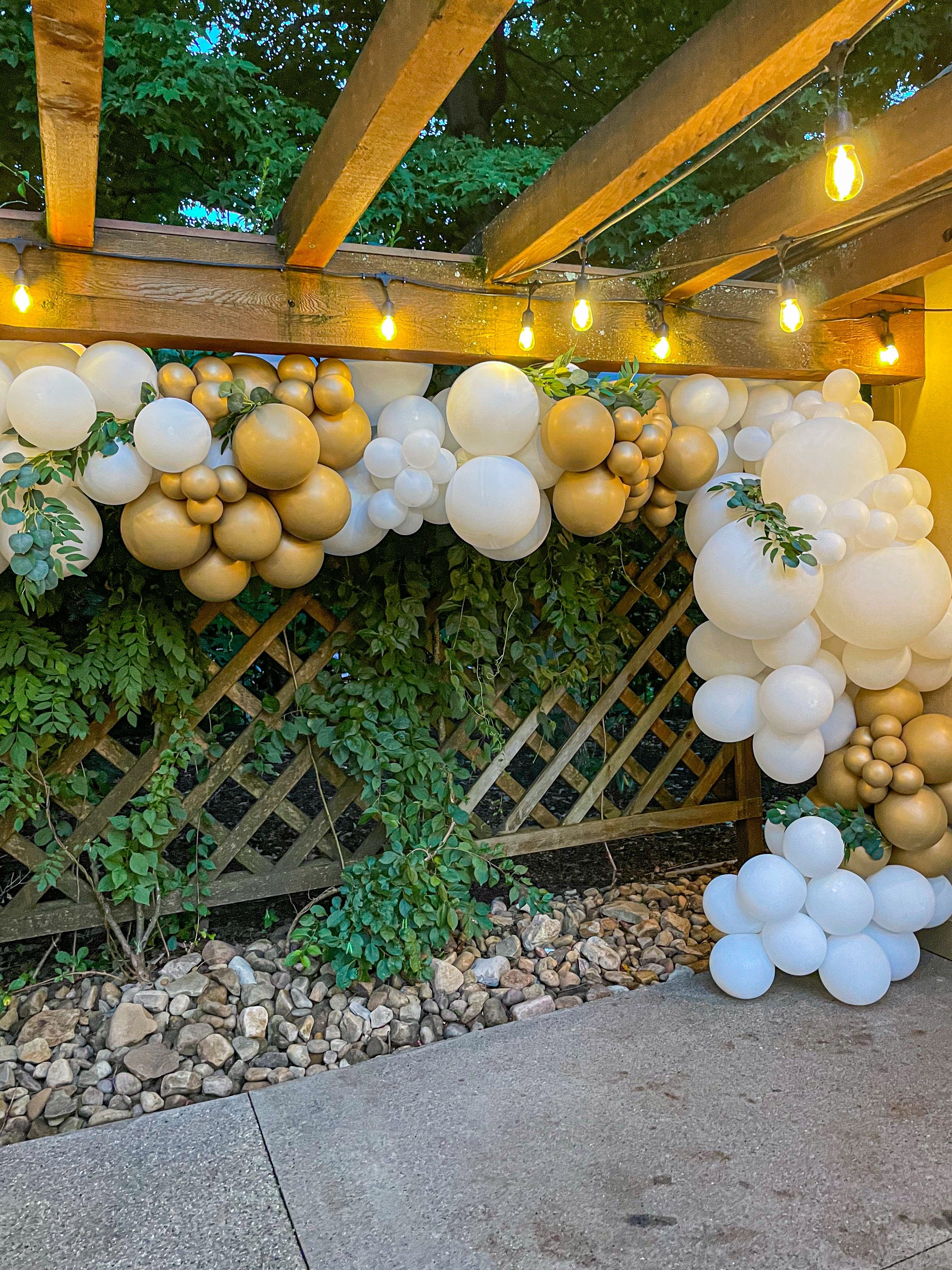 A white and old balloon garland on a porch with string lights.