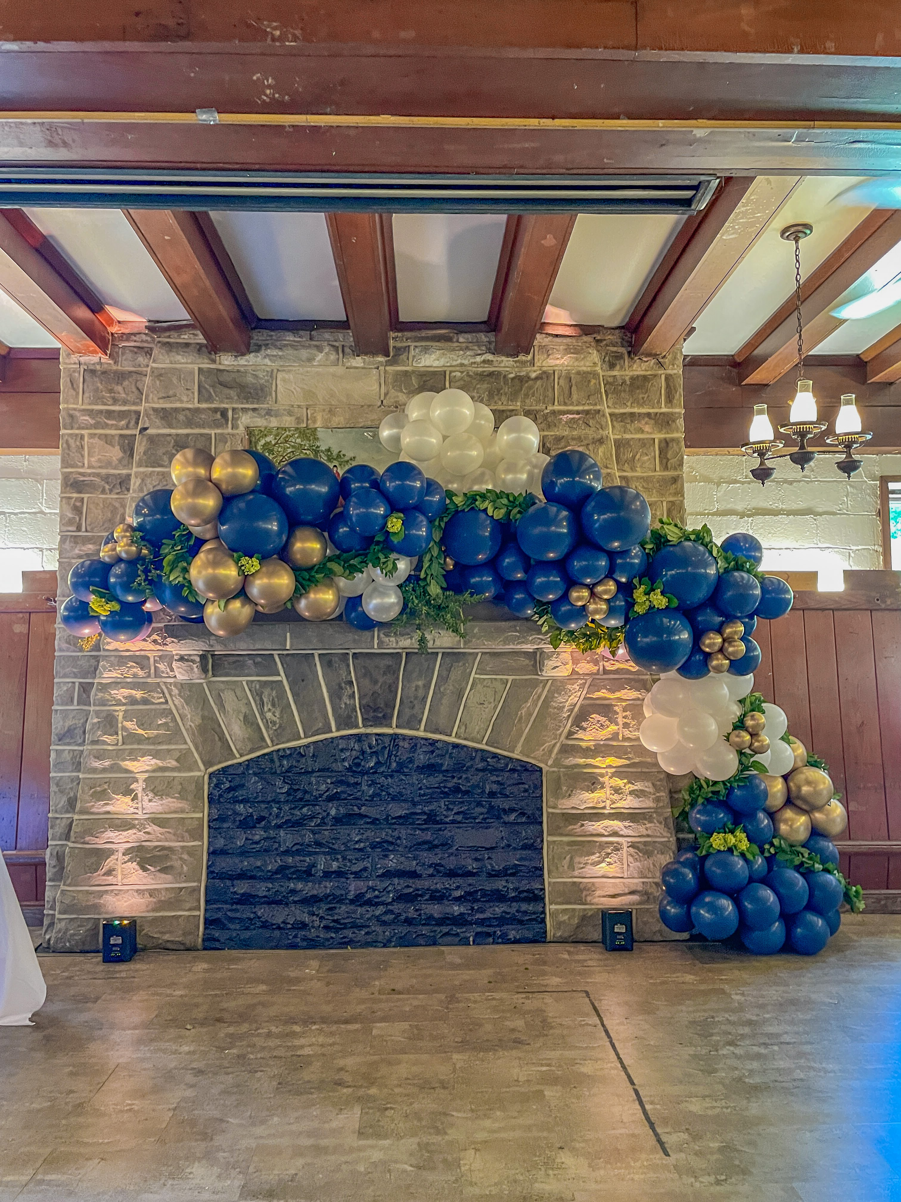 A blue, gold, and white balloon garland against a fireplace.