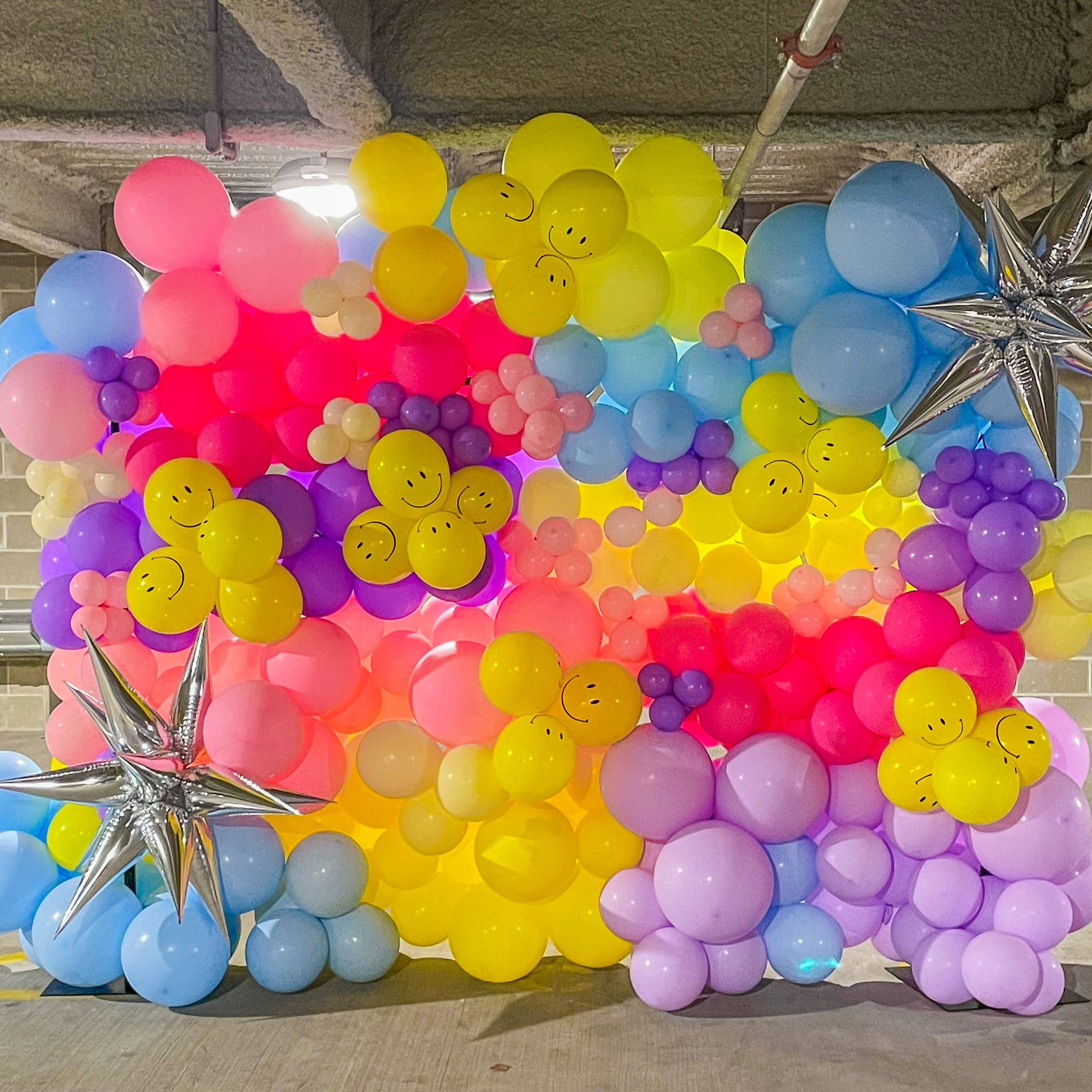 A bright colored balloon wall with yellow, blue, purple, and pink balloons.
