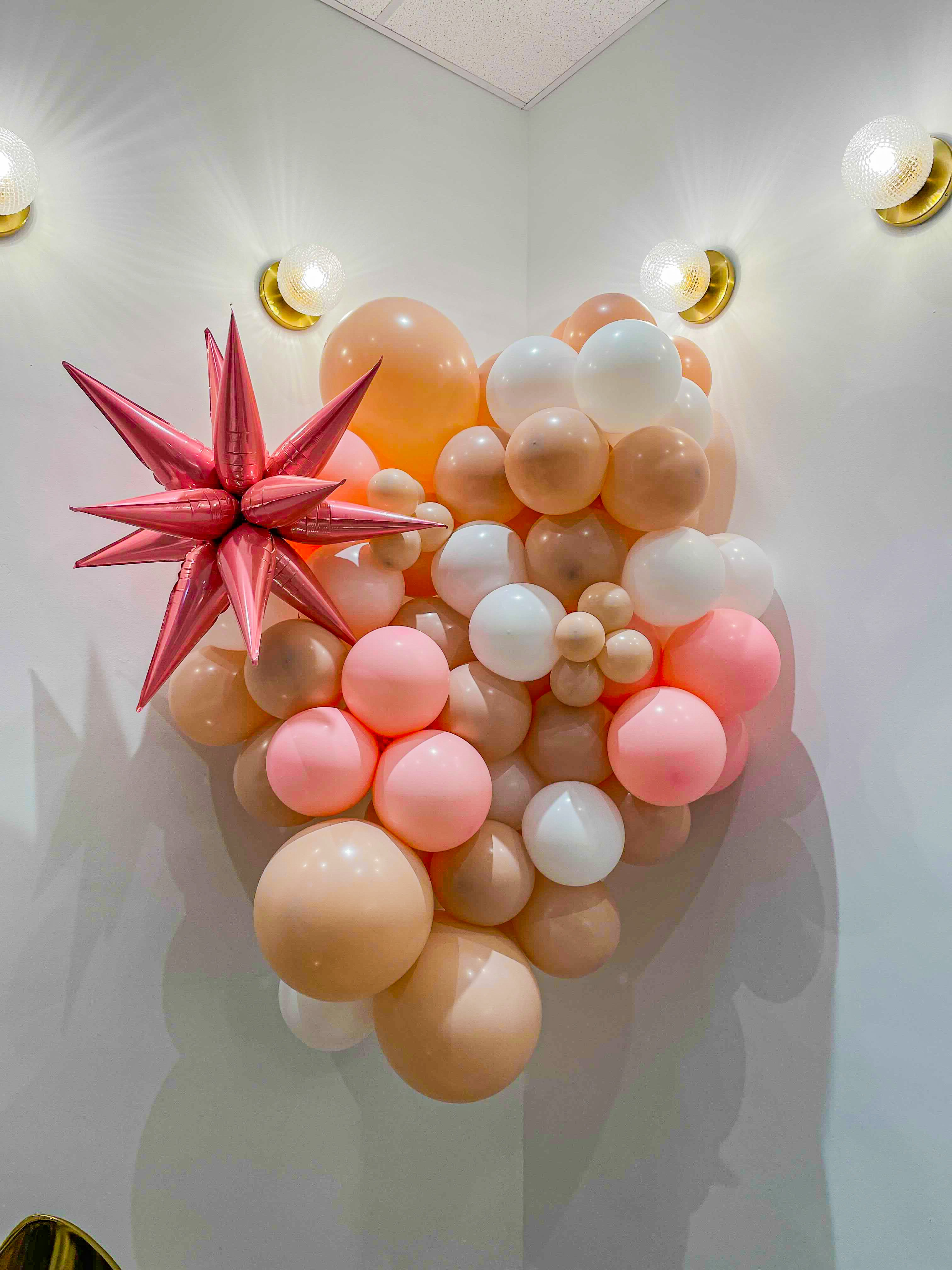 A peach, pink, and white balloon structure with a pink starburst balloon.