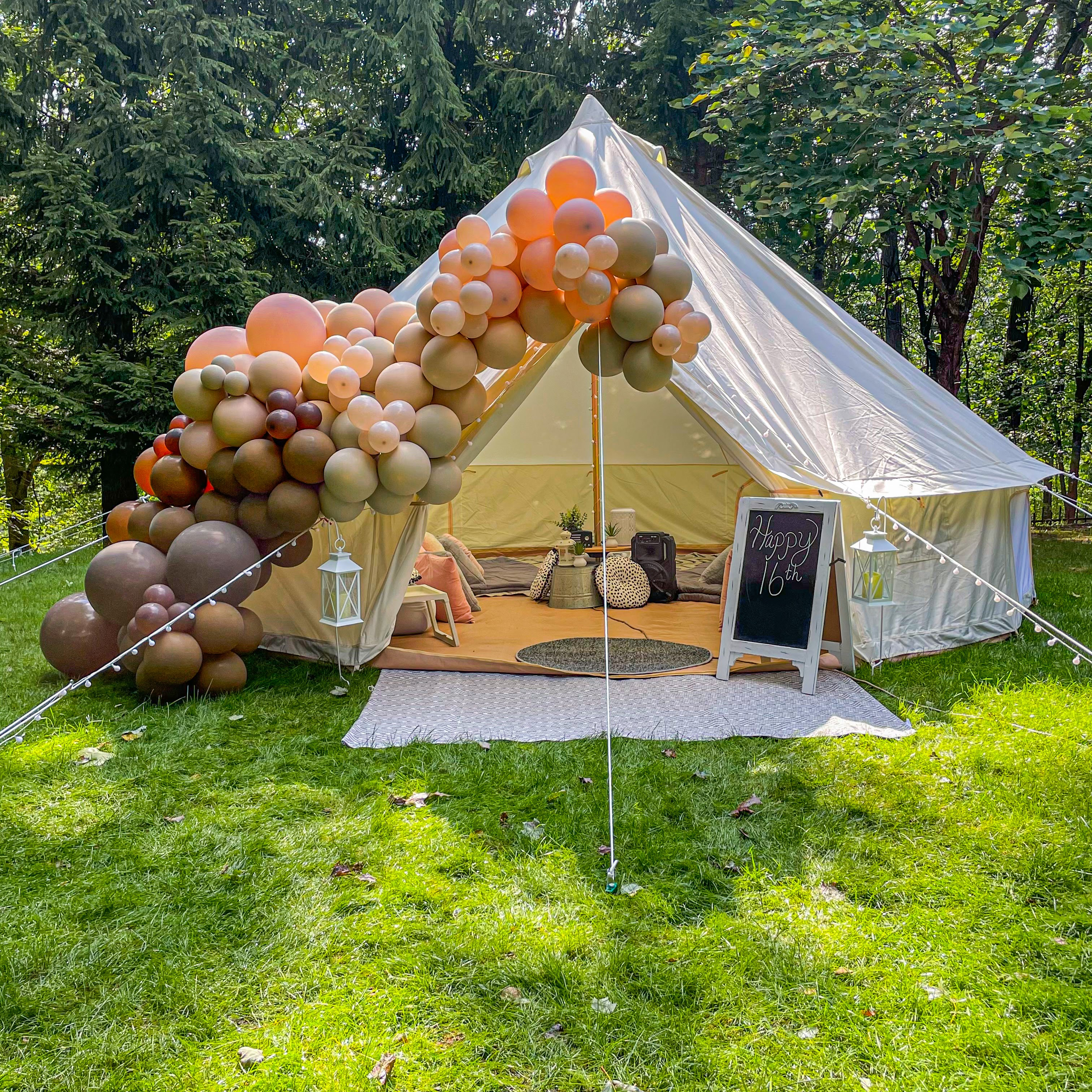 A bohemian tent with a neutral balloon garland going up the side of it.