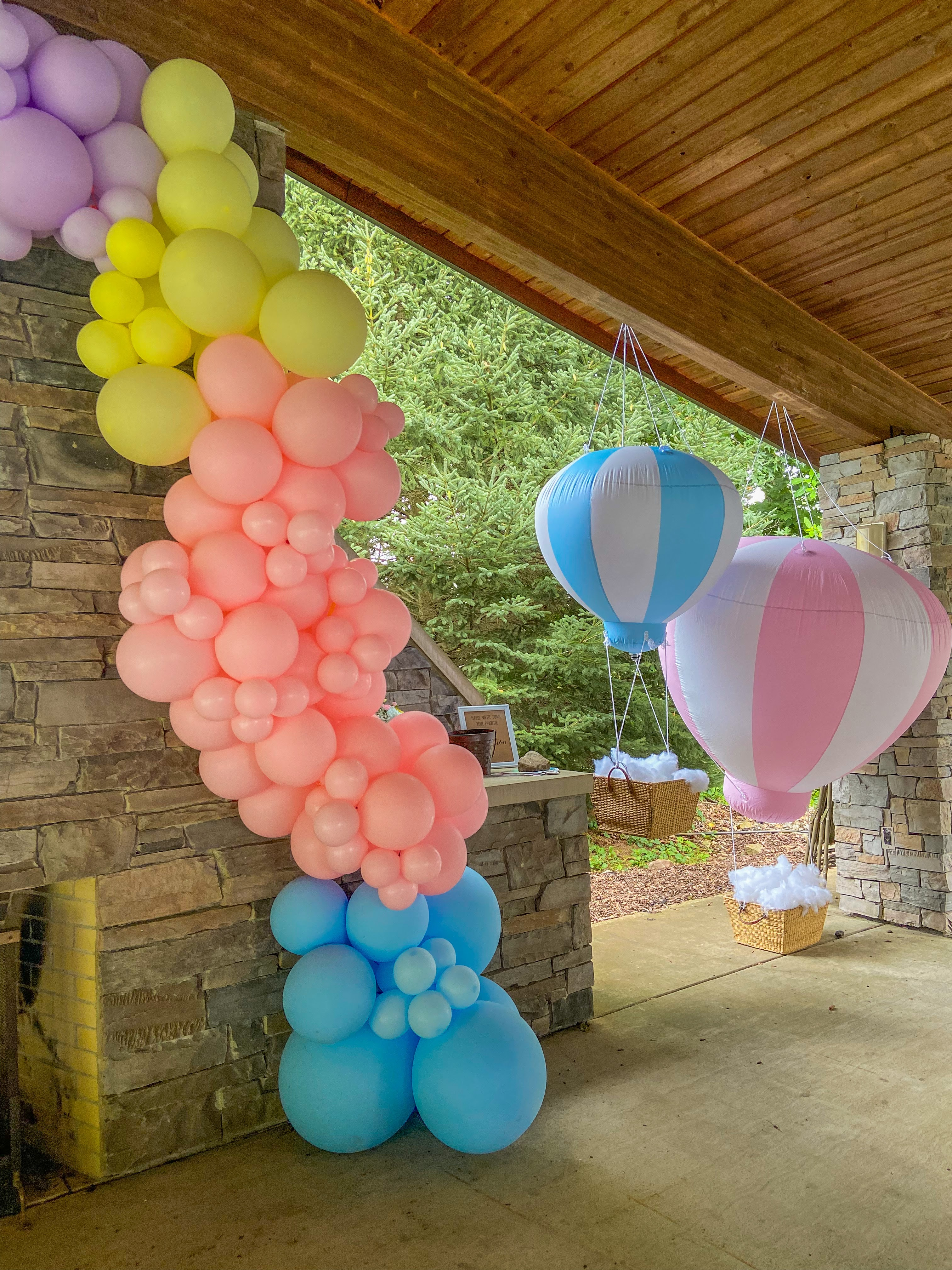 A pastel balloon garland with blue, pink, yellow, and purple balloons under a pavillion.