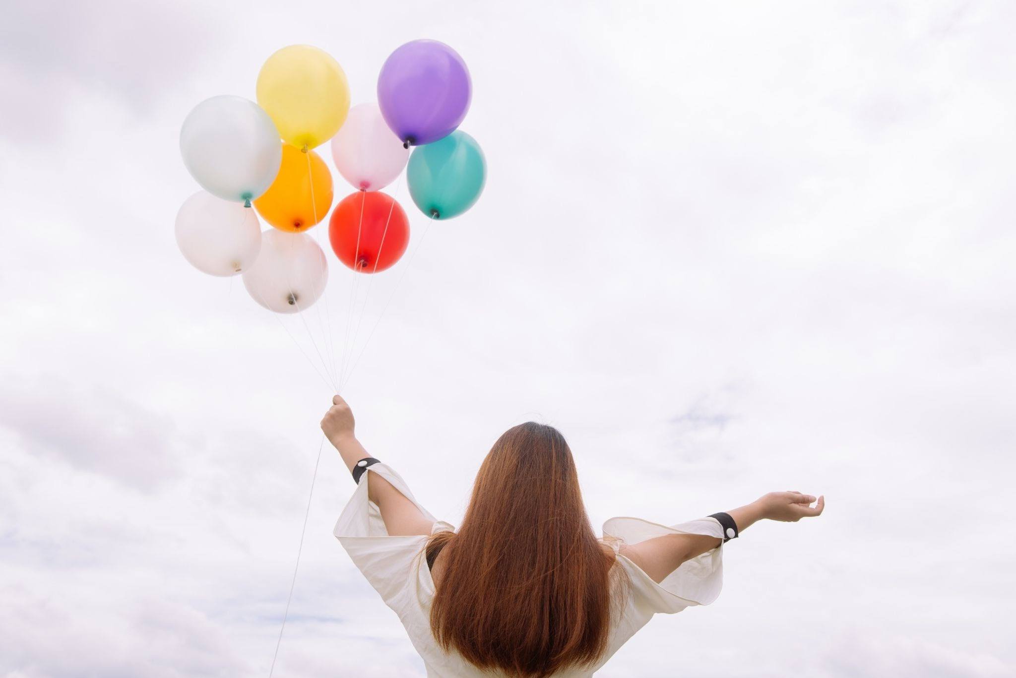 A girl standing outside holding a cluster of balloons.