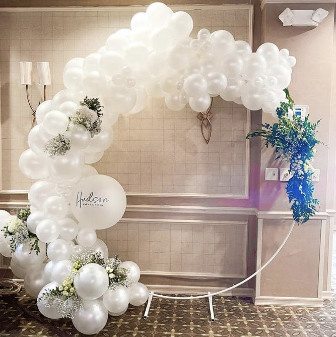 A balloon circle backdrop with white balloons, greenery, and white flowers.
