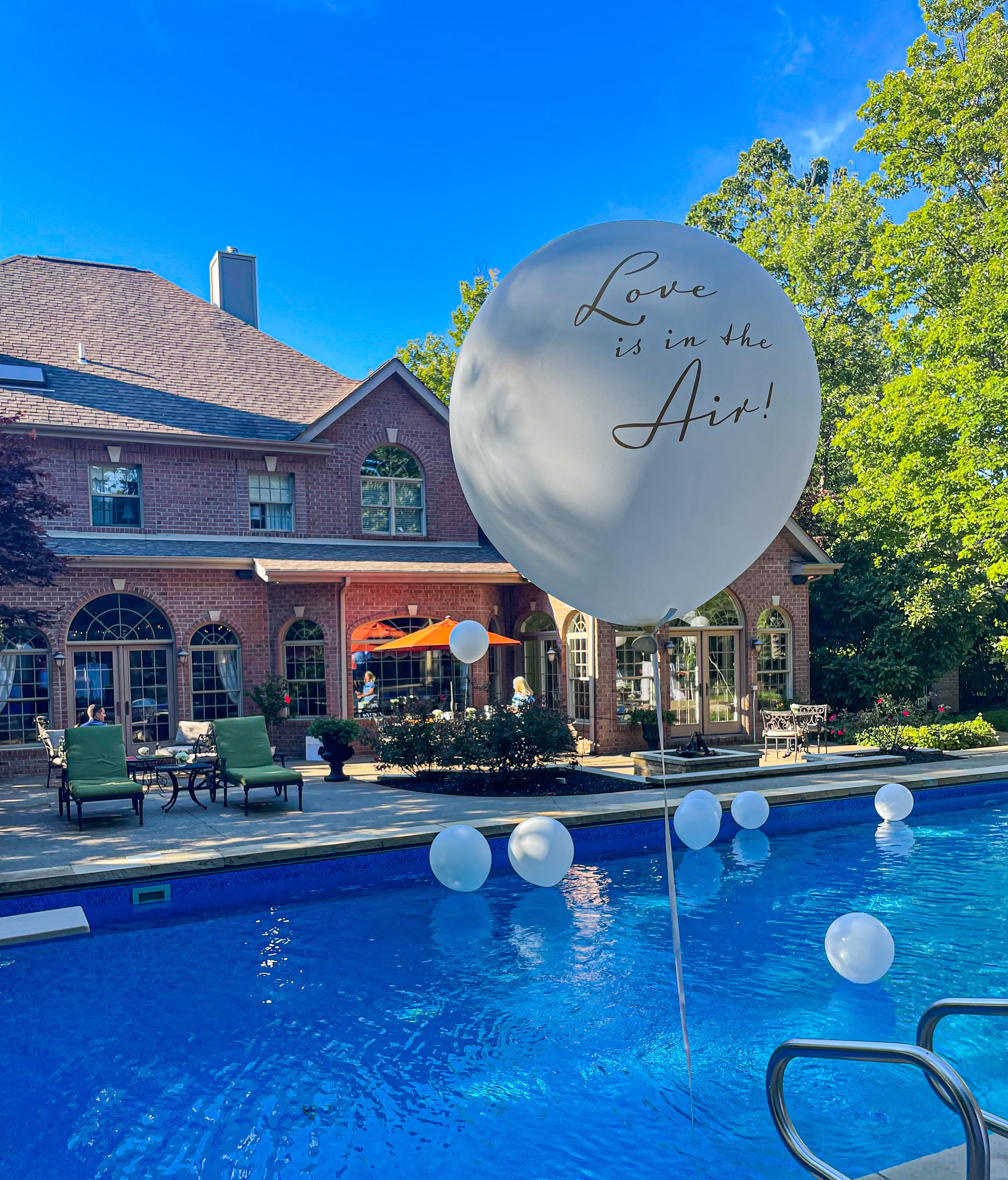 """A balloon that says """"Love is in the air"""" floating above a swimming pool."""