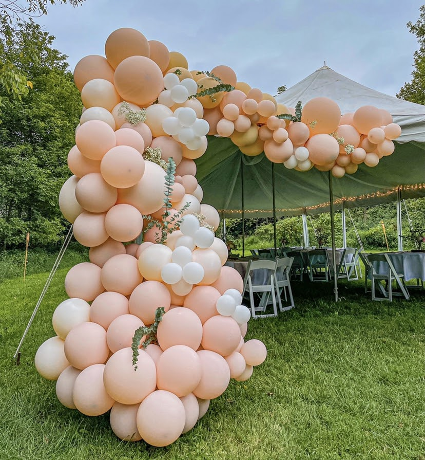 A peach and white balloon garland with greenery placed throughout it.