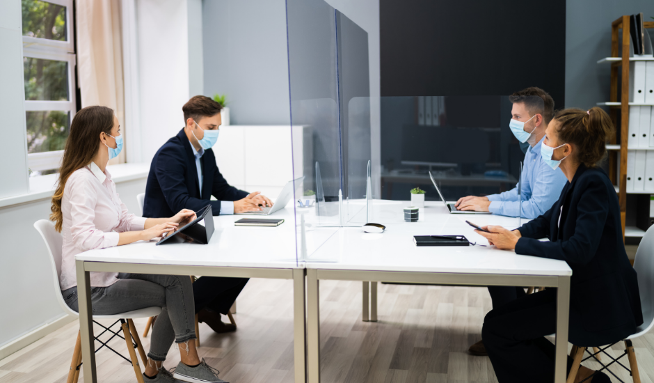 employees in a modern office with plastic dividers, wearing masks, socially distancing