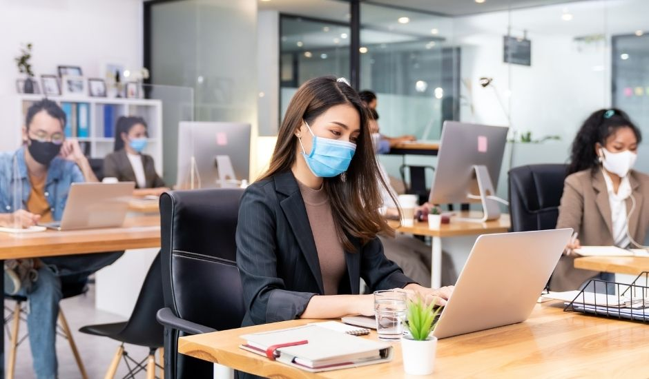 a female office worker wearing a mask in the office of a business
