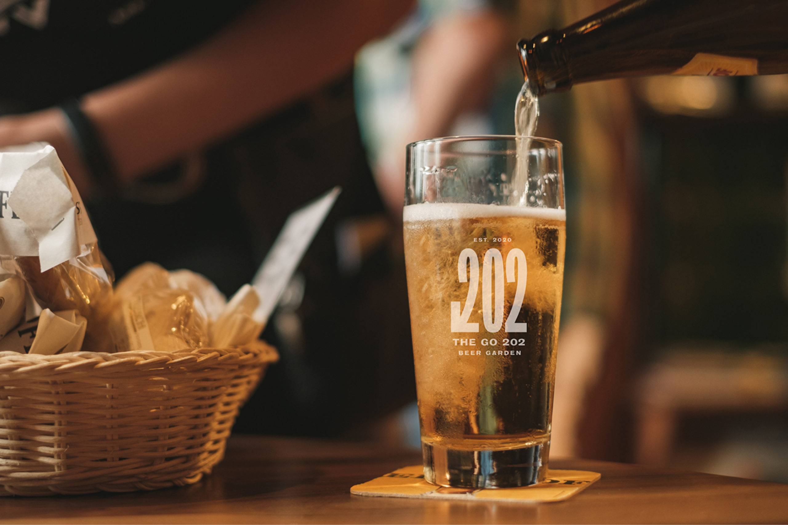 The Go 202 logo shown on a beer glass while beer is being poured from a bottle
