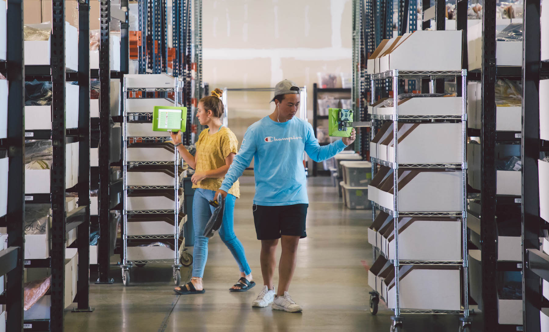 Two employees using WarehouseOS™ at the Roolee warehouse