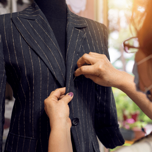 A student in TaF.tc's Pattern Drafting and Sewing - Jackets showcasing her pinstripe blazer jacket on a black mannequin.