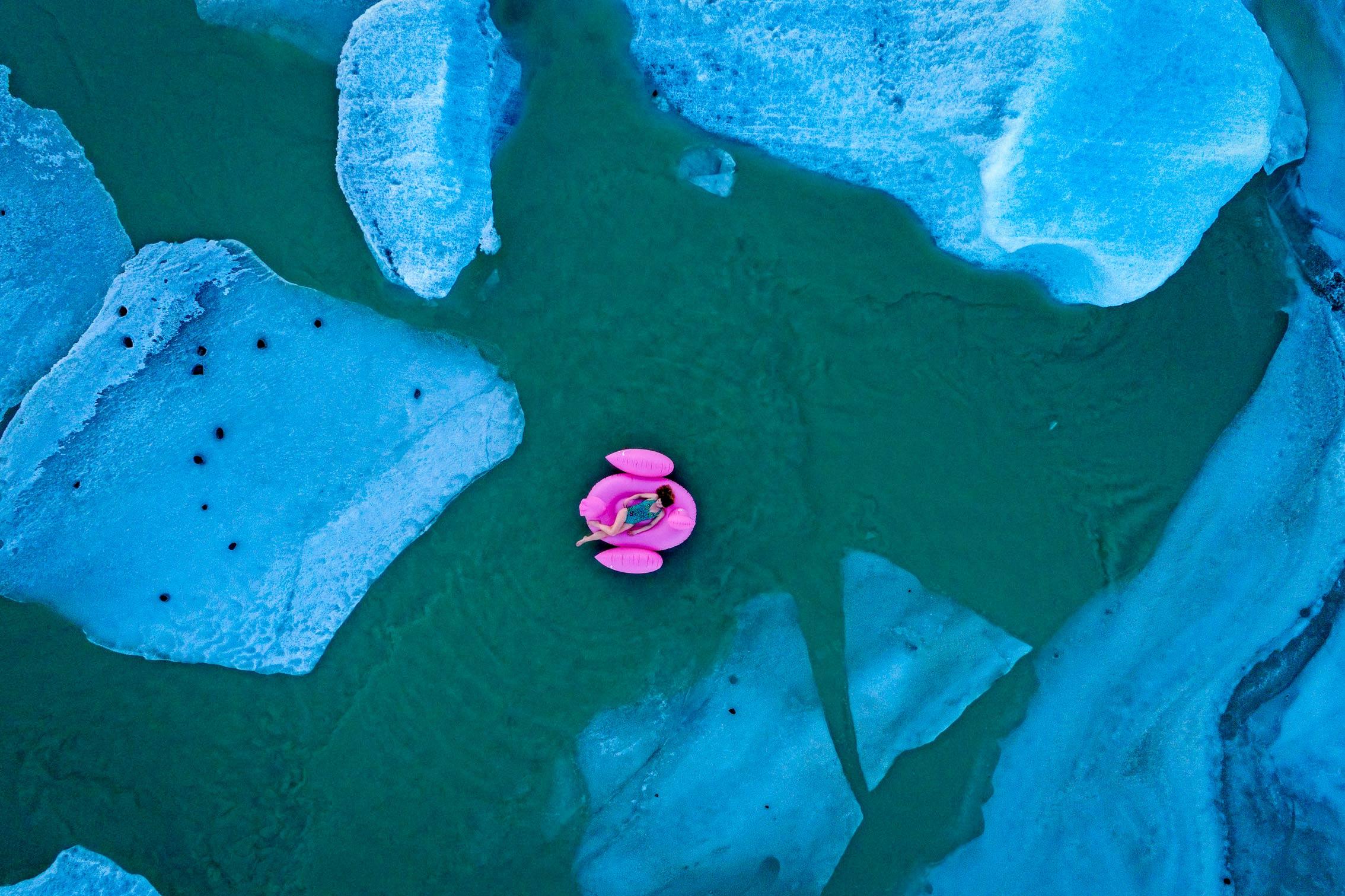 ©KontraPixel – woman on pink plastic flamingo floating in a glacier lagoon