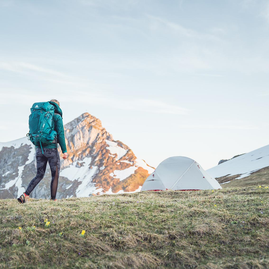 ©Lukas Reumschüssel – girl with huge backpack walking towards tent